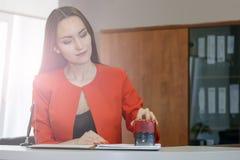 Segretario in un vestito rosso mette un bollo nei messaggi ricevuti lavoro d'ufficio, controllo del documento fotografia stock
