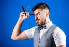 Segreti del barbiere Barbiere che tiene gli strumenti d'annata del barbiere Uomo barbuto con il rasoio e forbici in retro parrucc fotografie stock