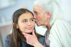 Segreti di sussurro della nonna e della bambina fotografia stock