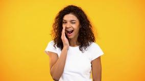 Segreti di sussurro sorridenti della donna e sbattere le palpebre sul fondo giallo della macchina fotografica, voci fotografia stock libera da diritti