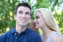 Segreto attraente delle coppie (fuoco sulla donna) Fotografia Stock