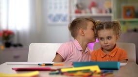 Segreto di sussurro del fratello alle sorelle orecchio, bambini comunicazione, pettegolante fotografie stock libere da diritti