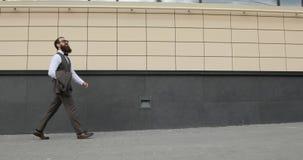 Segua il colpo dell'uomo d'affari Walking sulle vie del distretto aziendale archivi video