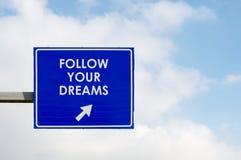 Segua le vostre parole di sogni visualizzate sul segnale stradale blu fotografia stock libera da diritti