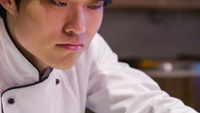 Seguendo colpo del cuoco unico asiatico sorridente che dà l'ultima volta stock footage