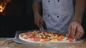 Seguendo il colpo del primo piano di collocazione della pizza non cotta con le guarnizioni dalla tavola farinosa sul metallo sbuc archivi video