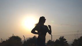 Seguimento à menina desportiva que movimenta-se na estrada secundária no nascer do sol Jovem mulher que corre fora na manhã Activ filme