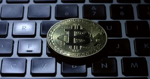 Seguimento após um bitcoin do casascius em um teclado preto do portátil vídeos de arquivo