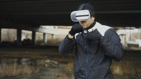 Seguimiento alrededor del tiro del hombre del boxeo en sacadores del entrenamiento de las auriculares de VR 360 en lucha de la re almacen de video