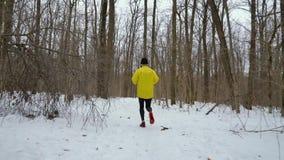Seguimiento del tiro del atleta del corredor que activa en bosque en día de invierno frío almacen de video