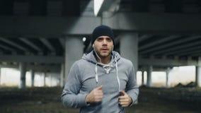 Seguimiento del tiro del corredor juguetón del hombre que pone en los auriculares y del comienzo que corre en la ubicación urbana almacen de metraje de vídeo