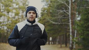 Seguimiento del tiro del hombre hermoso del corredor en los auriculares que activan mientras que la música que escucha en inviern metrajes