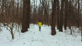 Seguimiento del tiro del hombre que activa en bosque en día de invierno frío almacen de metraje de vídeo