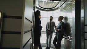 Seguindo o tiro das mulheres de negócios e dos colegas dos homens de negócios que falam no elevador e prepare para abaixar em mod