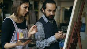 Seguindo o tiro de artista especializado equipe a moça de ensino para tirar pinturas e explicação dos princípios no estúdio da ar vídeos de arquivo