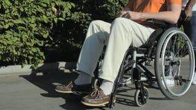 Seguindo o tiro de um homem agradável que anda com um homem wheelchaired video estoque