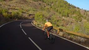 Seguindo o tiro video de um ciclista masculino que escala acima uma estrada da montanha Equipe fazer o treinamento do ciclismo em vídeos de arquivo