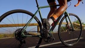 Seguindo o tiro video de um ciclista masculino que escala acima uma estrada da montanha Equipe fazer o treinamento do ciclismo em filme