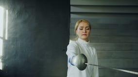 Seguir o tiro dos jovens concentrou o treinamento da mulher do esgrimista que cerca o exercício no estúdio dentro vídeos de arquivo