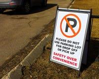 A segurança sobre a conveniência assina dentro um lote da escola com um veículo estacionado ilegalmente ao lado dela fotografia de stock