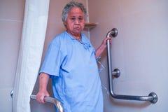 Seguran?a paciente asi?tica do punho do banheiro do toalete do uso da mulher superior ou idosa da senhora idosa na divis?o de hos fotos de stock