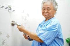 Seguran?a paciente asi?tica do punho do banheiro do toalete do uso da mulher superior ou idosa da senhora idosa na divis?o de hos imagem de stock royalty free