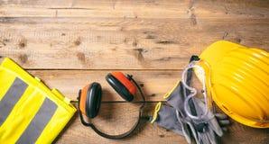 Seguridad de construcción Casco, auriculares, guantes y vidrios protectores en el fondo de madera, espacio de la copia, visión su Foto de archivo