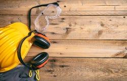 Seguridad de construcción Casco, auriculares, guantes y vidrios protectores en el fondo de madera, espacio de la copia, visión su Fotos de archivo