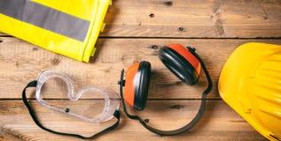 Seguridad de construcción Casco, auriculares y vidrios protectores en el fondo de madera, espacio de la copia, visión superior Fotografía de archivo