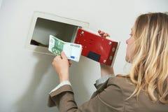 Seguridad del dinero La mujer puso efectivo de los ahorros en la caja fuerte de la pared fotografía de archivo libre de regalías