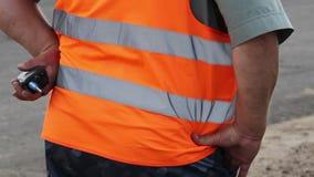 Seguridad masculina gorda torpe con walky-talky en uniforme de la naranja almacen de video