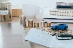 Seguro de coche y concepto del préstamo: Llave del coche en el banco del libro en el escritorio con el ahorro del dinero en el ah Foto de archivo
