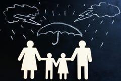 Seguro de vida Figuras exhaustas de la lluvia y de la familia debajo del paraguas imagen de archivo
