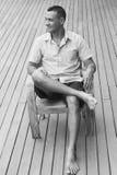 Seguro y sólido El hombre joven hermoso que se sienta en una silla de madera y que mira una cámara con un piso de madera en un fo Imagen de archivo libre de regalías