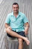 Seguro y sólido El hombre joven hermoso que se sienta en una silla de madera y que mira una cámara con un piso de madera en un fo Fotografía de archivo libre de regalías