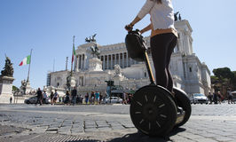 Segway in Venice square (Piazza Venezia - Roma). A girl is riding a segway in Rome in Piazza Venezia, the famous square in Rome. In the background is the altar Royalty Free Stock Image