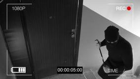 Sehen Sie CCTV als Einbrecher, der herein durch die Tür mit einer Brechstange bricht Stockbild