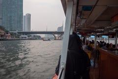 Sehen Sie die Bürogebäude, die Brücken und den bewölkten Himmel vom Boot an stockfotografie