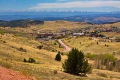 Sehen Sie die Unterlassung der Stadt des Krüppel-Nebenflusses, Colorado mit Bergen im Hintergrund an Stockfotografie