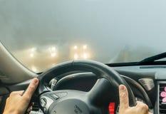 Sehen Sie durch die Autowindschutzscheibe im Winternebel auf der Straße an Stockbilder