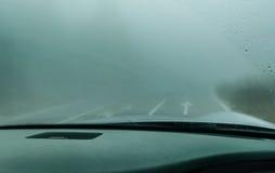 Sehen Sie durch die Autowindschutzscheibe im Winternebel auf der Straße an Lizenzfreies Stockbild