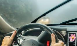 Sehen Sie durch die Autowindschutzscheibe im Winternebel auf der Straße an Stockfotos