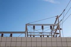 Sehen Sie einer Blockwand und einer Nebenstelle der elektrischen Leistung oben betrachten gegen blauen Himmel an Stockbilder