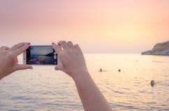 Sehen Sie Landschaftssonnenuntergang an einem intelligenten Mobiltelefon an Stockfotos