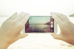 Sehen Sie Landschaftssonnenuntergang an einem intelligenten Mobiltelefon an Stockbilder