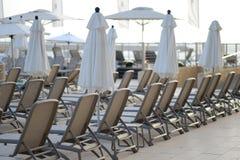 Sehen Sie Poolbett, Strandstuhl mit Regenschirmwagenaufenthaltsräumen nahe dem Pool an stockbilder