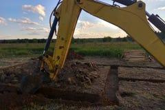 Sehen Sie von oben genanntem an Arbeitsbagger Tractor Digging einen Graben an stockfotos