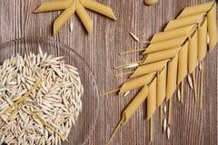 Sehen Sie von oben nach unten auf den Teigwaren und den Körnern des Weizens mit Kopienraum über verwittertem Holztisch an Stockfotografie
