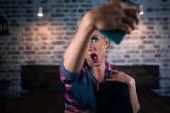 Sehr überraschte junge Frau, die in camera vom Smartphone schaut Stockfoto