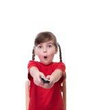 Sehr überraschtes kleines Mädchen, das rotes t-kurzes und haltenes Fernsehen bezüglich trägt Lizenzfreie Stockbilder